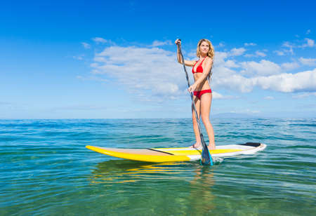 active lifestyle: Attractive Young Woman Stand Up Paddle Surfing In Hawaii, Beautiful Tropical Ocean, Active Beach Lifestyle Stock Photo