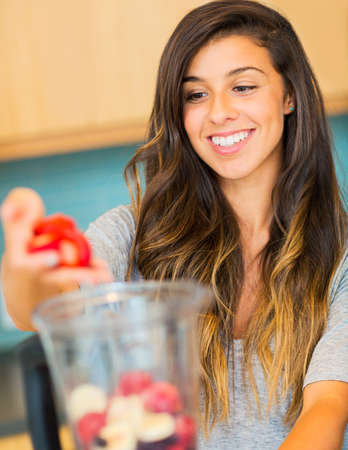 Woman Making Fresh Fruit Smoothie photo