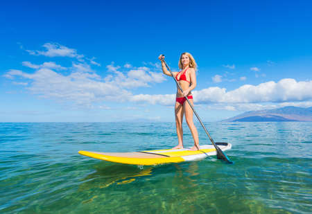 Attractive Young Woman Stand Up Paddle Surfing In Hawaii, Beautiful Tropical Ocean, Active Beach Lifestyle Imagens