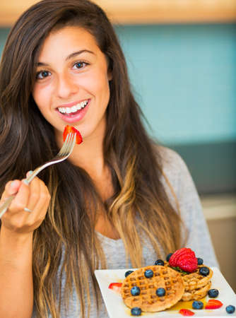 Woman Eating Waffles with Fresh Fruit for Breakfast photo