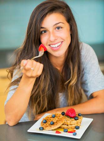 Woman Eating Waffles with Fresh Fruit for Breakfast Stock fotó