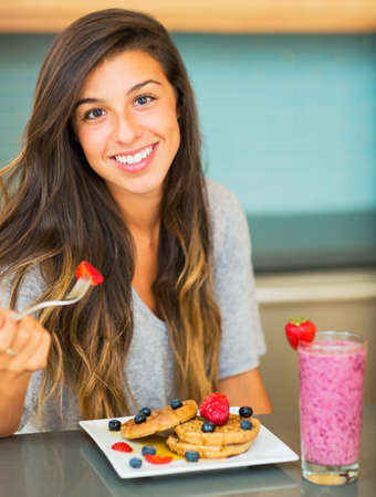 Woman Eating Waffles with Fresh Fruit for Breakfast Stock Photo