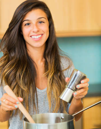 Beautiful Young Woman Cooking Dinner at Home photo