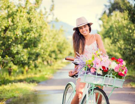 Mooie jonge vrouw op de fiets in het park