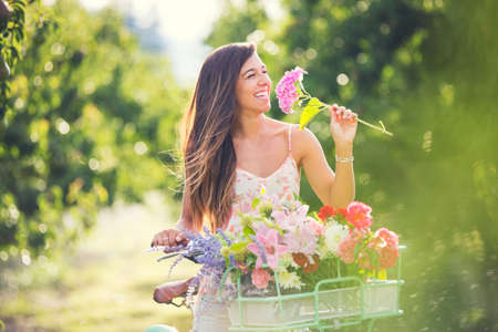 Beautiful young woman smelling flowers on bike in park Stock Photo