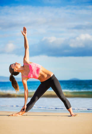 Young woman practicing yoga on the beach at sunset, Wellness Concept Healthy Lifestyle photo