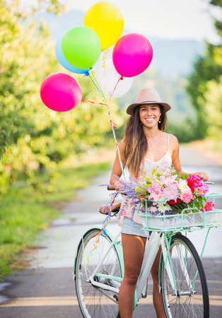 Beautiful young woman on bike in park with balloons photo