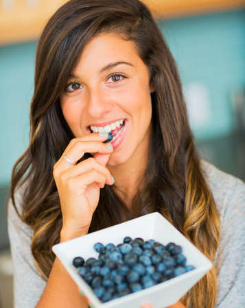 Portrait of beautiful young woman eating a bowl of blueberries and smiling photo