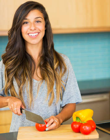 woman knife: Beautiful young woman cutting vegitables, preparing healthy dinner at home Stock Photo
