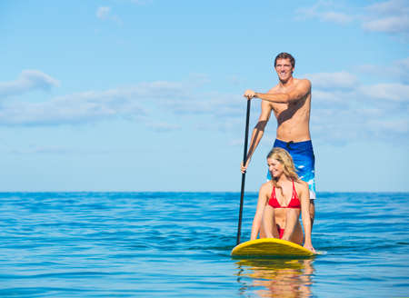 Couple Stand Up Paddle Surfing In Hawaii, Beautiful Tropical Ocean, Active Beach Lifestyle Stock Photo