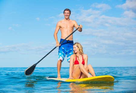 paddleboard: Couple Stand Up Paddle Surfing In Hawaii, Beautiful Tropical Ocean, Active Beach Lifestyle Stock Photo
