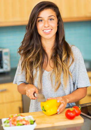 Beautiful young woman cutting vegitables, preparing healthy dinner at home Banco de Imagens