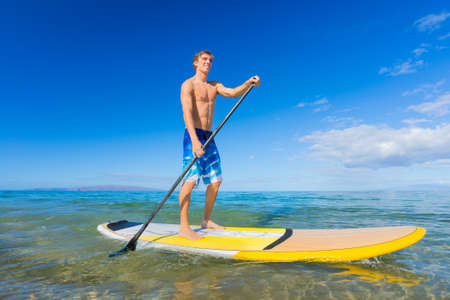 Attractive Young Man Stand Up Paddle Surfing In Hawaii, Beautiful Tropical Ocean, Active Beach Lifestyle photo