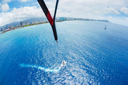 parasailing: Parasailing Over Ocean in Hawaii, View from up in the Sky