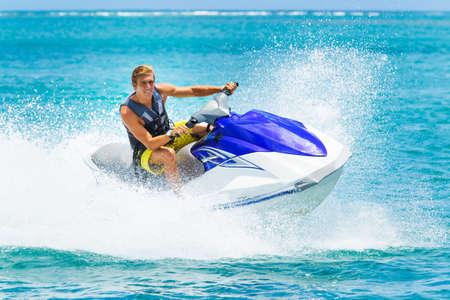 jet ski: Hombre joven en la moto de agua, Oc�ano Tropical, Vacation Concept