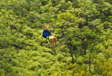 zip: Man on Zipline over Lush Tropical Valley
