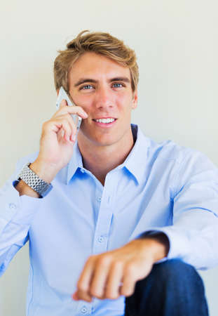 Young Handsome Attractive Business Man Smiling Talking on Smart Phone photo