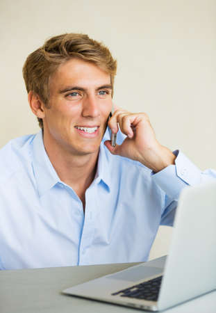 Attractive Young Man Working on Laptop Computer Talking on Phone  photo