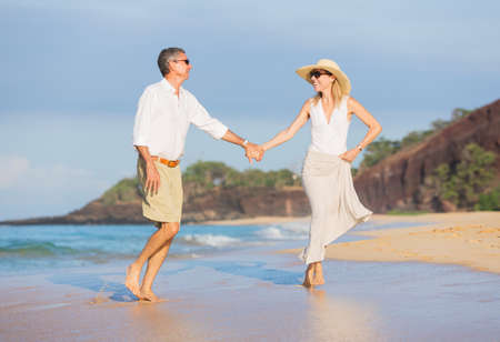 Happy Romantic Middle Aged Couple Enjoying Walk on the Beach, Vacation Retirement Concept photo