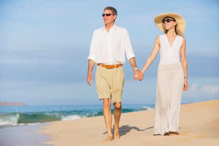 Happy Romantic Middle Aged Couple Enjoying Walk on the Beach photo