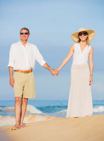 Happy Romantic Middle Aged Couple Enjoying Walk on the Beach photo