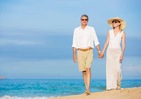 Happy Romantic Couple Walking on the Beach Stock Photo