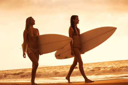 Beautiful Surfer Girls Walking on the Beach at Sunset in Hawaii photo