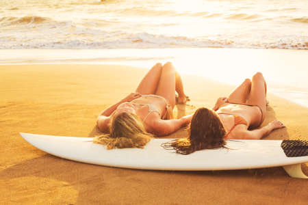 Beautiful Surfer Girls on the Beach at Sunset photo