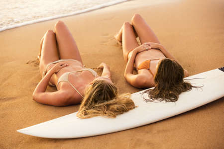 Beautiful Sexy Surfer Girls on the Beach at Sunset photo
