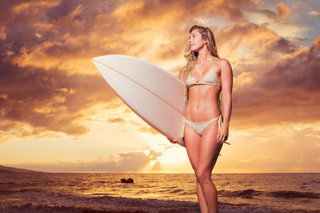 Beautiful sexy surfer girl in bikini on the beach at sunset photo