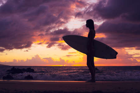 Beautiful sexy surfer girl in bikini on the beach at sunset, silhouette photo