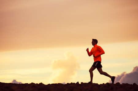 男性ランナー シルエット、日没、カラフルな夕焼け空に走っている男
