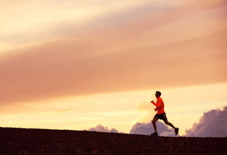 Male runner silhouette, Man running into sunset, colorful sunset sky  photo