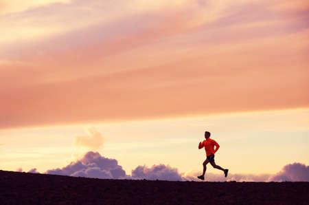 男性ランナー シルエット、日没、カラフルな夕焼け空に走っている人