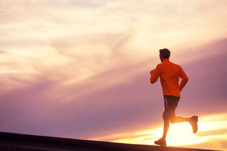 Mężczyzna biegacz sylwetka, Człowiek działa w zachód słońca, zachód słońca, niebo, kolorowy Zdjęcie Seryjne