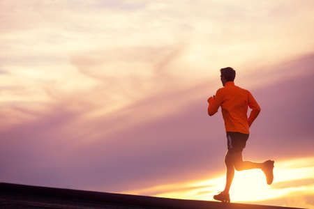 Male runner silhouette, Man running into sunset, colorful sunset sky  Archivio Fotografico