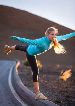 Young attractive athletic woman, wearing sporty cloths on trail, practicing yoga at sunset photo