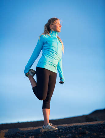 Young attractive athletic woman, wearing sporty cloths on trail, stretching before run photo