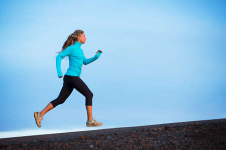 fitness goal: Athletic woman jogging outside, training outdoors. Running on road at sunset Stock Photo