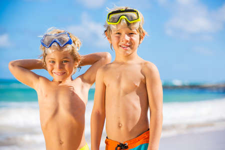 Two young boys having fun on tropical beach, happy best friends playing photo