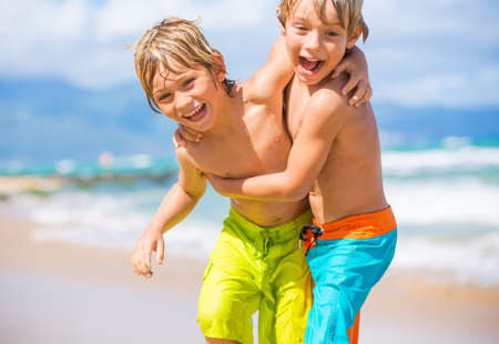 fun: Two young boys having fun on tropical beach, happy best friends playing Stock Photo