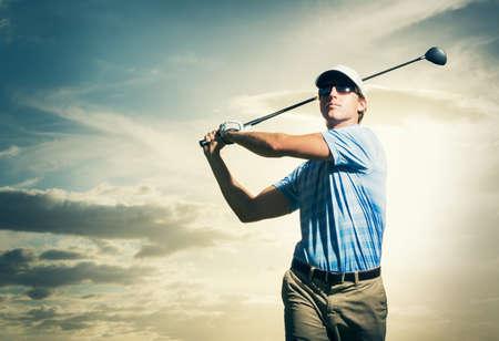 日没で、劇的な夕焼け空のゴルフクラブを振る男性ゴルファー