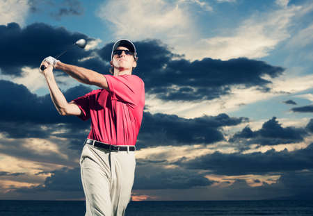 Golfer at sunset, Man swinging golf club with dramatic sunset sky backdrop photo
