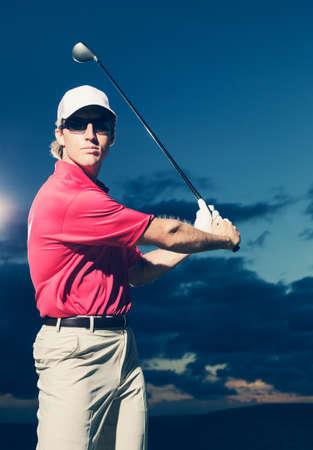 Golfspeler bij zonsondergang, Man swingende golfclub met dramatische zonsondergang hemel achtergrond Stockfoto