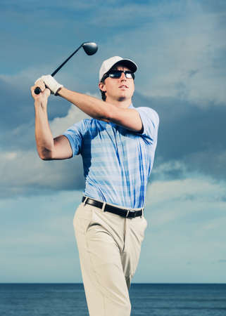 Golfer at sunset, Man swinging golf club with dramatic blue sky  photo