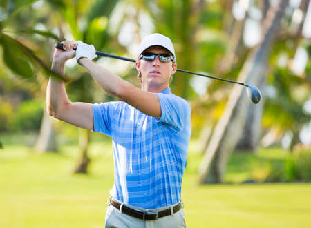 Athletic young man playing golf, golfer hitting fairway shot, swinging club photo