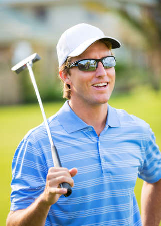 Athletic young man playing golf, Portrait of Golfer on Course with putter photo