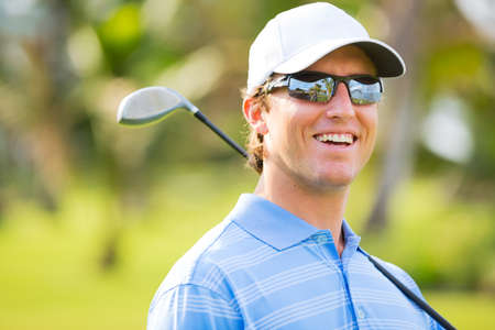 Athletic young man playing golf, Portrait of Golfer on Course with driver photo