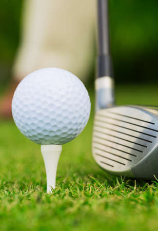 Close up view of golf ball on tee on golf course photo