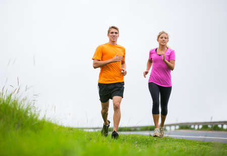 Fitness sport couple jogging outside, training together outdoors. Running on road
